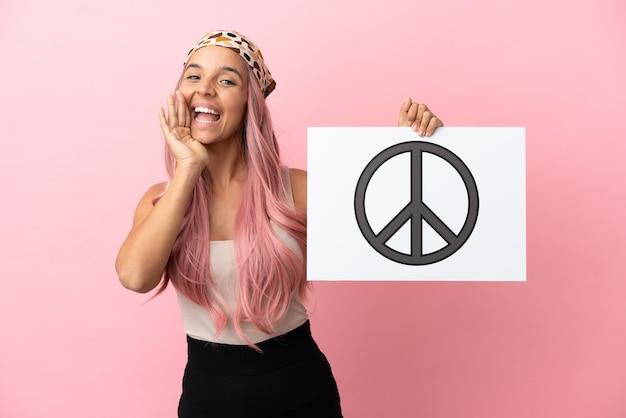 Młoda kobieta rasy mieszanej z różowymi włosami na różowym tle trzymająca tabliczkę z symbolem pokoju i krzyczącą