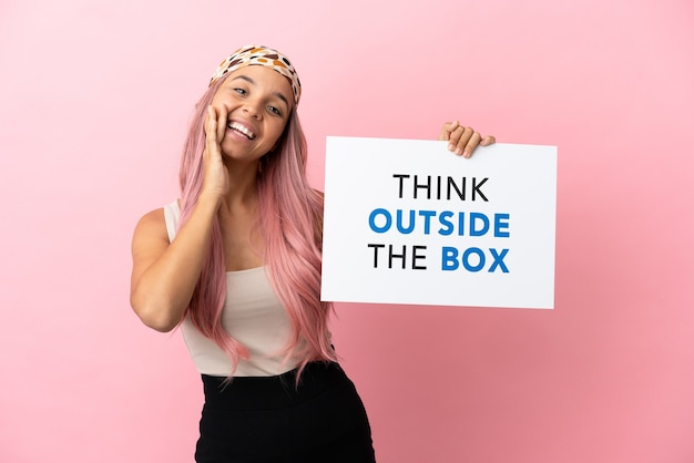 Młoda kobieta rasy mieszanej z różowymi włosami na różowym tle trzymająca tabliczkę z tekstem think outside the box i krzycząca