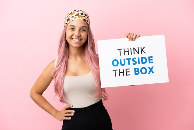 Młoda kobieta rasy mieszanej z różowymi włosami na różowym tle trzymająca tabliczkę z tekstem think outside the box ze szczęśliwym wyrazem twarzy
