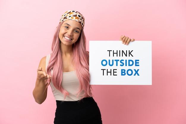 Młoda kobieta rasy mieszanej z różowymi włosami na różowym tle, trzymająca tabliczkę z tekstem think outside the box