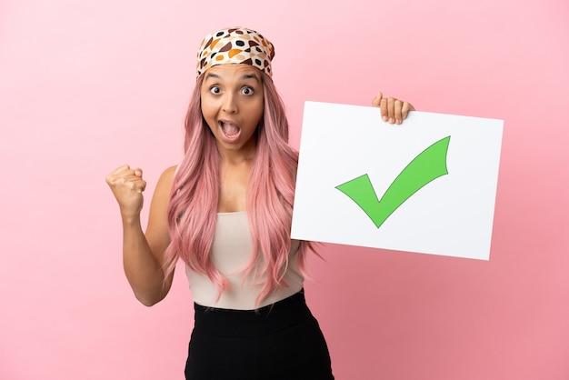 Młoda kobieta rasy mieszanej z różowymi włosami na różowym tle trzymająca tabliczkę z tekstem zielona ikona znacznika wyboru i świętująca zwycięstwo