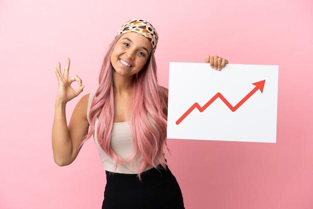 Młoda kobieta rasy mieszanej z różowymi włosami na różowym tle trzymająca znak z rosnącym symbolem strzałki statystyk z ok znakiem