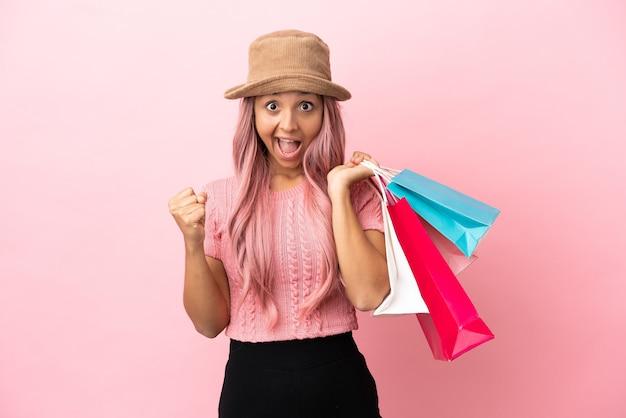 Młoda kobieta rasy mieszanej z torbą na zakupy odizolowana na różowym tle świętująca zwycięstwo w pozycji zwycięzcy