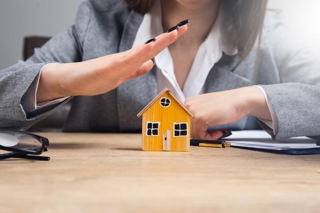 Młoda kobieta ręce chroniące model domu na stole