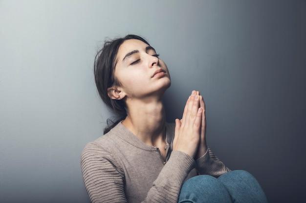 Młoda kobieta ręce modląc się do boga