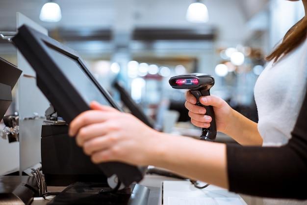 Młoda kobieta ręce skanuje / wprowadza rabat / sprzedaż na paragonie, kasa z ekranem dotykowym, rynek / sklep