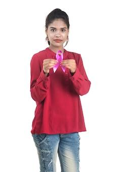 Młoda kobieta ręce trzymając różową wstążkę świadomości raka piersi