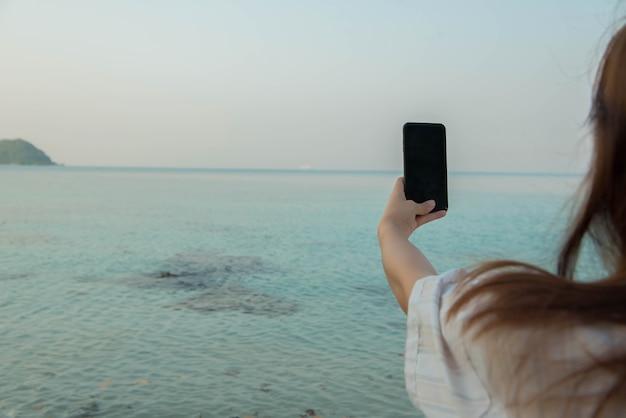 Młoda kobieta ręce używają smartfona siedzącego na skale, ciesząc się plażą