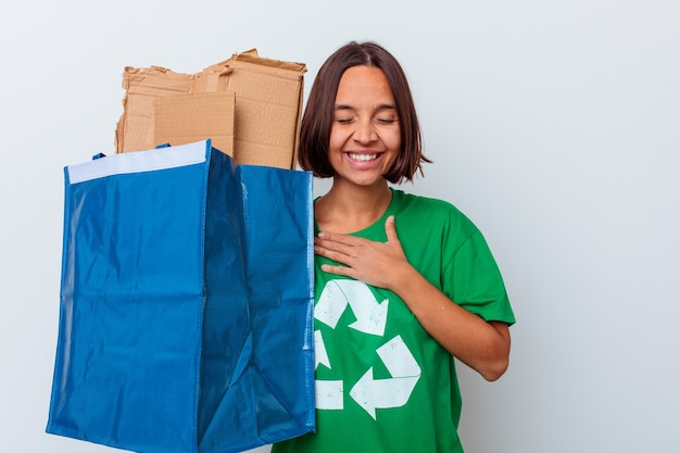 Młoda kobieta recykling kartonu na białej ścianie śmieje się głośno, trzymając rękę na klatce piersiowej