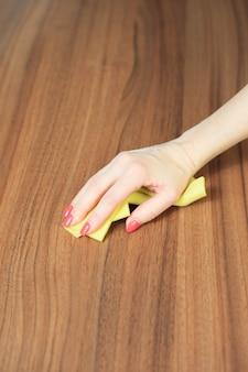 Młoda kobieta ręcznie czyści nowoczesny stół z drewna ściereczką do kurzu