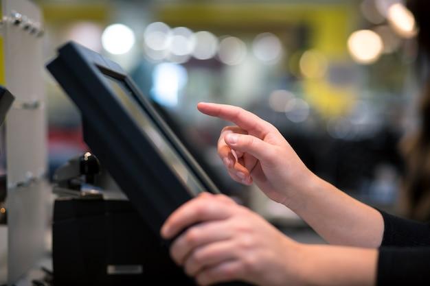 Młoda kobieta ręcznie robi proces płatności w kasie z ekranem dotykowym, koncepcja finansów