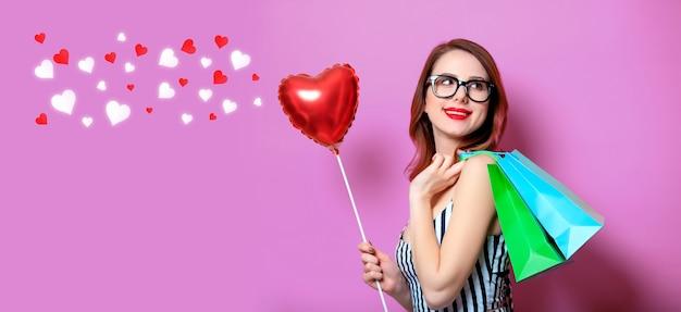 Młoda kobieta red-haired z zabawką w kształcie serca i torby na zakupy na żółtym tle