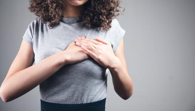 Młoda kobieta ręka na ból serca.