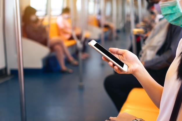 Młoda kobieta ręka trzyma i używa telefonu komórkowego w pociągu metra ze ścieżką przycinającą na wyświetlaczu