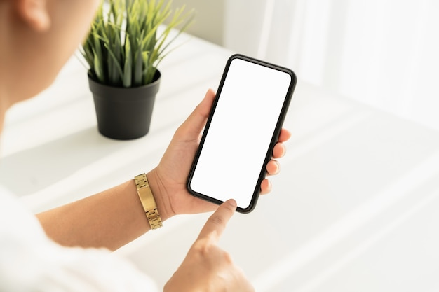 Młoda kobieta ręka trzyma smartfon na stole i na ekranie jest pusta, koncepcja sieci społecznej.