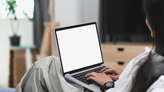 Młoda kobieta relaks na kanapie i przy użyciu komputera przenośnego makiety pusty biały ekran.