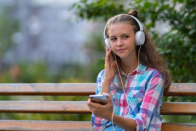 Młoda kobieta, relaks na ławce na świeżym powietrzu, słuchanie muzyki na słuchawkach stereo, patrząc z boku z przemyślanym wyrazem twarzy