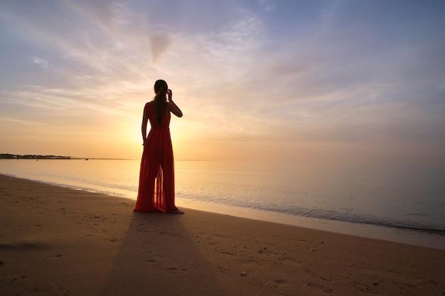 Młoda kobieta, relaks samotnie na brzegu oceanu piasku nad morzem, ciesząc się ciepłym tropikalnym wieczorem.