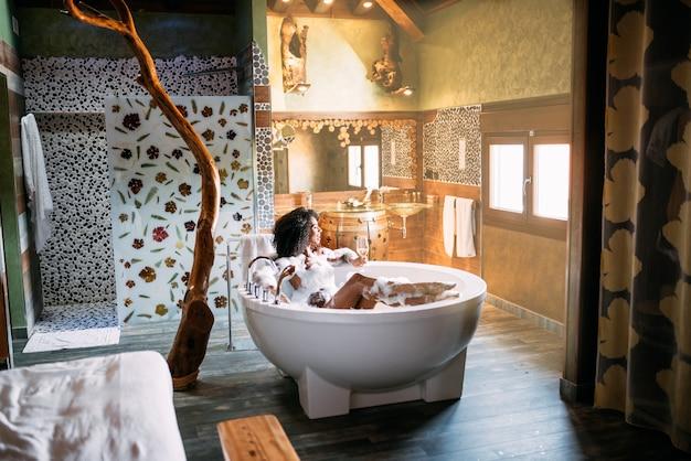 Młoda kobieta relaks w kąpieli z hydromasażem pokryte pianką