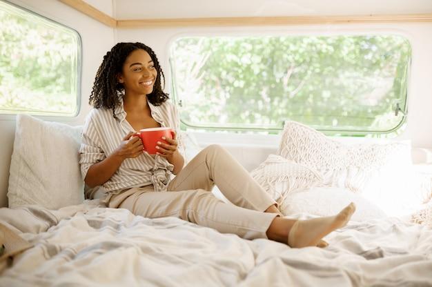 Młoda kobieta relaks w łóżku, kemping w przyczepie. para podróżuje furgonetką, romantyczne wakacje w kamperze, wakacje w kamperze
