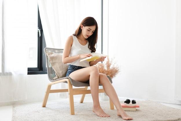 Młoda kobieta relaksująca czytanie książki w domu