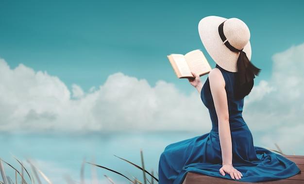 Młoda kobieta relaksująca z natury latem siedząca na tarasie i czytająca książkę harmonia living