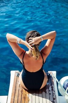 Młoda kobieta relaksuje na jachcie na morzu przy słonecznym dniem