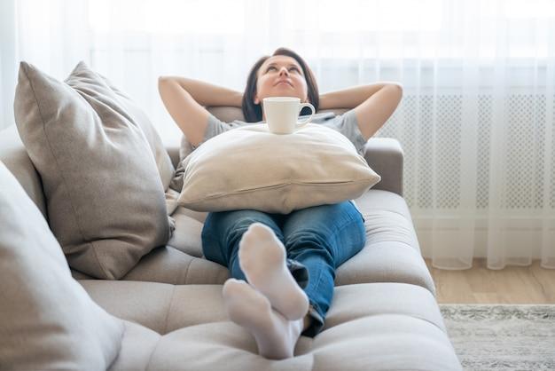 Młoda kobieta relaksuje na jej leżance z filiżanką kawy na poduszce