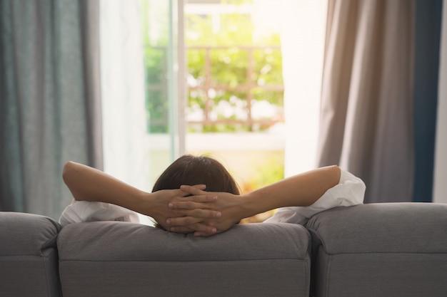 Młoda kobieta relaksuje na kanapie przy wygodnym domowym i przyglądającym outside w żywym pokoju