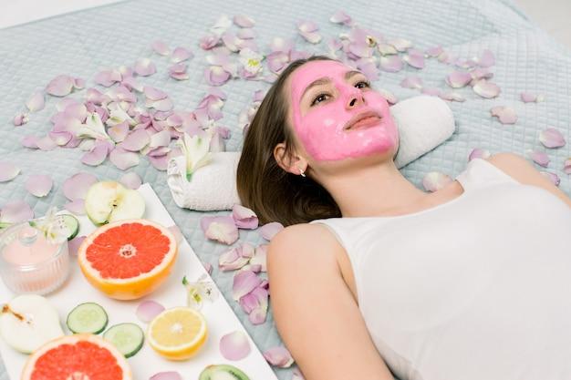 Młoda kobieta relaksuje na łóżku z różową borowinową kosmetyk maską na twarzy przy piękno salonem indoors. wokół dziewczyny płatki kwiatów, plasterki cytryny, grejpfruta, kiwi i jabłka