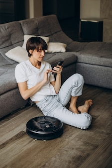 Młoda kobieta relaksuje się, gdy robot odkurza podłogę