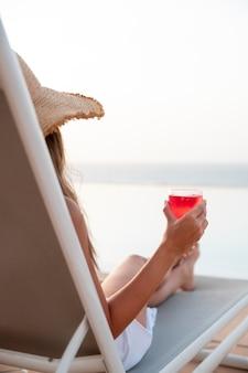 Młoda kobieta relaksuje się przy basenie, delektując się koktajlem