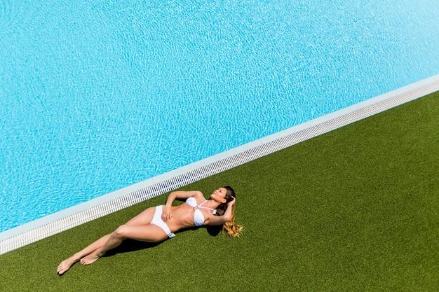 Młoda kobieta relaksuje się przy basenie?