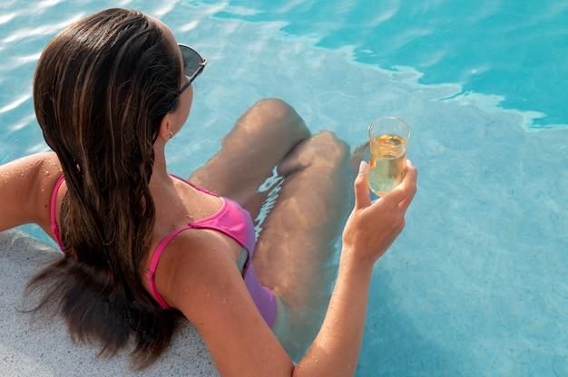 Młoda kobieta relaksuje się samotnie w basenie?