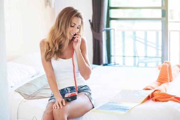 Młoda kobieta relaksuje się w hotelu i dzwoni do obsługi pokoju