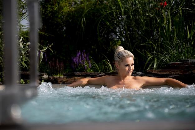 Młoda kobieta relaksuje się w jacuzzi