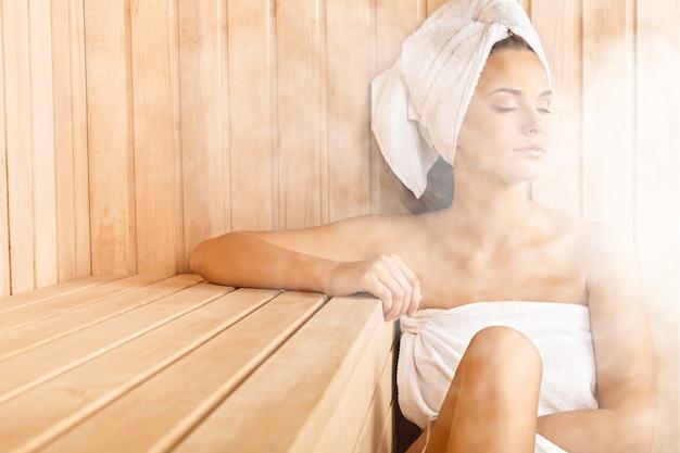 Młoda kobieta relaksuje się w saunie
