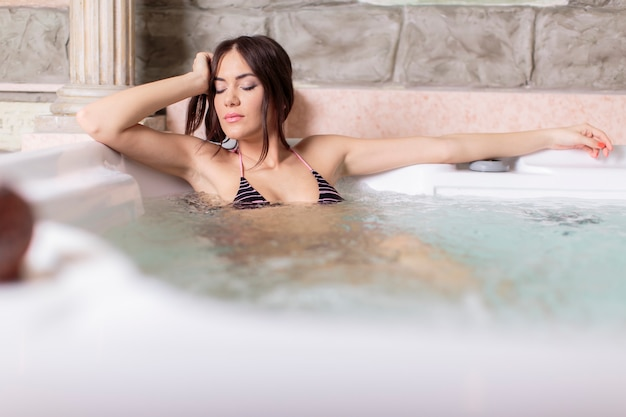 Młoda kobieta relaksuje w gorącej balii