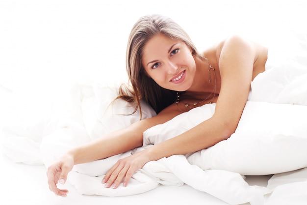 Młoda kobieta relaksuje w łóżku przy rankiem