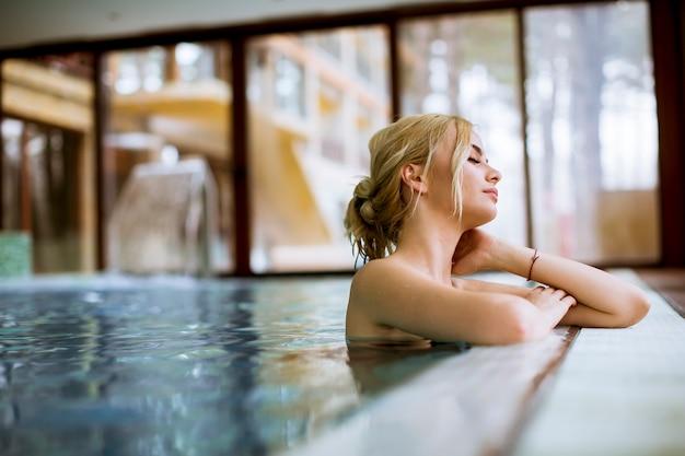 Młoda kobieta relaksuje w zdroju pływackim basenie