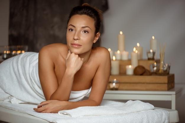 Młoda kobieta relaksuje w zdroju salonie.