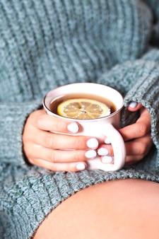 Młoda kobieta relaksuje z herbacianą filiżanką pod ręką