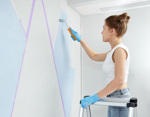Młoda kobieta remontuje dom malując ścianę za pomocą wałka do malowania i używając taśmy maskującej, stojąc na