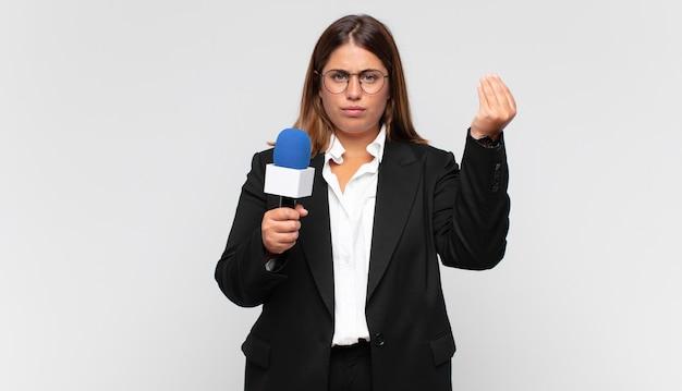Młoda kobieta reporter robi gest capice lub pieniądze
