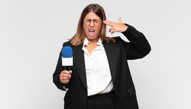 Młoda kobieta reporter szuka nieszczęśliwej i zestresowanej, samobójczy gest czyniąc znak pistoletu ręką, wskazując na głowę