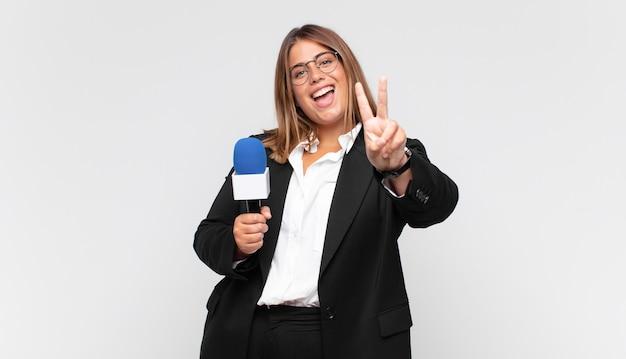 Młoda kobieta reporterka uśmiechnięta i wyglądająca przyjaźnie, pokazująca numer dwa lub sekundę z ręką do przodu, odliczający w dół