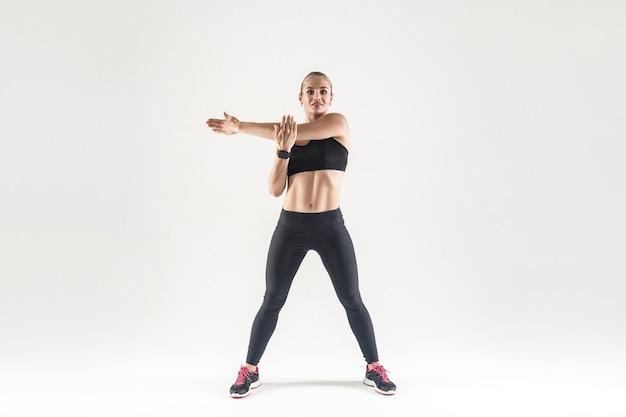 Młoda kobieta robi aerobik ćwiczenia i patrząc na kamery. strzał w pomieszczeniu, szare tło