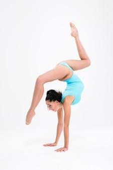 Młoda kobieta robi akrobatyczny wyczyn na białym tle na białej ścianie