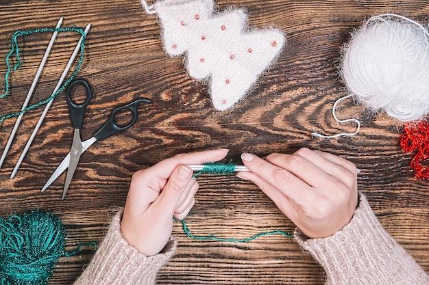 Młoda kobieta robi boże narodzenie ręcznie robione zabawki na drewnianym stole
