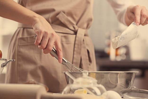 Młoda kobieta robi ciasto w kuchni, zbliżenie